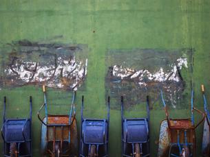 コンクリート塀に立て掛かる一輪車の写真素材 [FYI04672621]