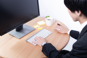 デスクトップパソコンを操作するビジネスマンの手元の写真素材 [FYI04672930]