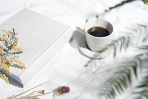 植物の影が差し込む窓辺と白い布とコーヒーカップのある写真素材の写真素材 [FYI04672949]