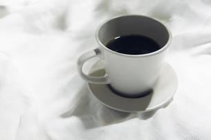 植物の影が差し込む窓辺と白い布とコーヒーカップのある写真素材の写真素材 [FYI04672954]