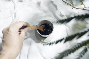 植物の影が差し込む窓辺と白い布とコーヒーカップのある写真素材の写真素材 [FYI04672962]