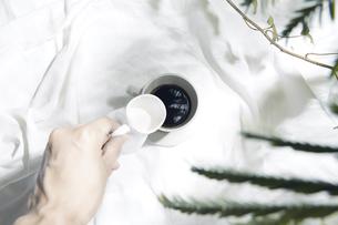 植物の影が差し込む窓辺と白い布とコーヒーカップのある写真素材の写真素材 [FYI04672966]