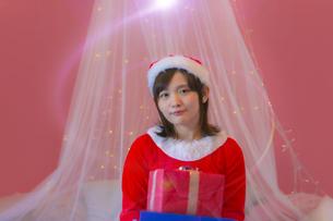 プレゼントを持つサンタ衣装の女性の写真素材 [FYI04673532]