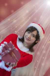 プレゼントを差し出すサンタ衣装の女性の写真素材 [FYI04673533]