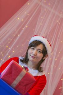 プレゼントを持つサンタ衣装の女性の写真素材 [FYI04673545]