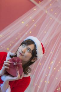 プレゼントを差し出すサンタ衣装の女性の写真素材 [FYI04673551]