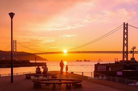 関西の風景 神戸市 明石海峡大橋と夕陽のアニメのような町並みの写真素材 [FYI04674058]
