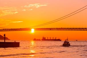 関西の風景 神戸市 明石海峡大橋と夕陽のアニメのような町並みの写真素材 [FYI04674059]