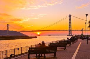 関西の風景 神戸市 明石海峡大橋と夕陽のアニメのような町並みの写真素材 [FYI04674060]