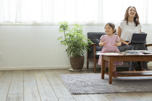 タブレットPCを操作する母親とそばで遊ぶ女の子の写真素材 [FYI04674443]