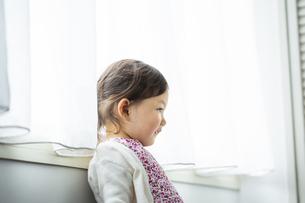 窓辺に寄り掛かる女の子の写真素材 [FYI04674471]