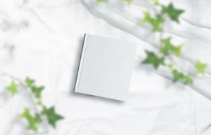 白背景の生成りの生地のアルバム冊子と植物グリーンのイラスト素材 [FYI04674475]
