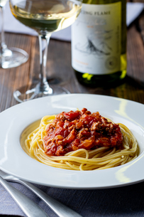 Pasta with meat and tomato sauce on wooden table.の写真素材 [FYI04674533]
