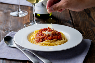 Pasta with meat and tomato sauce on wooden table.の写真素材 [FYI04674534]