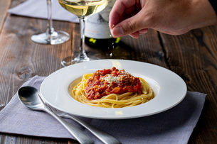 Pasta with meat and tomato sauce on wooden table.の写真素材 [FYI04674535]