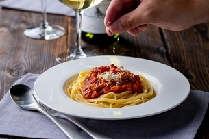 Pasta with meat and tomato sauce on wooden table.の写真素材 [FYI04674536]