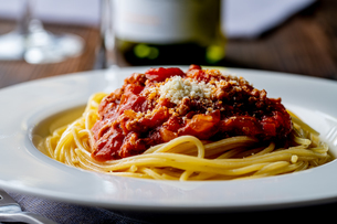 Pasta with meat and tomato sauce on wooden table.の写真素材 [FYI04674537]