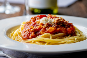 Pasta with meat and tomato sauce on wooden table.の写真素材 [FYI04674538]