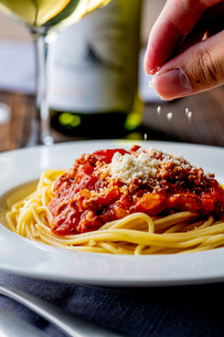 Pasta with meat and tomato sauce on wooden table.の写真素材 [FYI04674540]