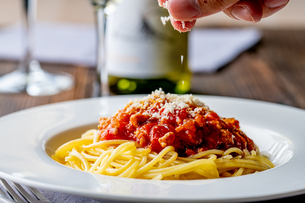 Pasta with meat and tomato sauce on wooden table.の写真素材 [FYI04674541]