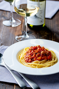 Pasta with meat and tomato sauce on wooden table.の写真素材 [FYI04674547]