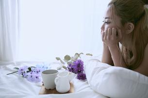 爽やかな朝に寝室のベッドでくつろぐ女性の写真素材 [FYI04675255]