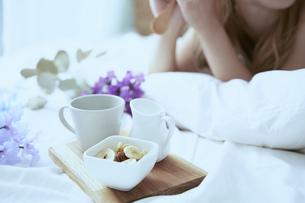 爽やかな朝に寝室のベッドでくつろぐ女性の写真素材 [FYI04675259]