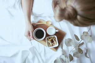 爽やかな朝に寝室のベッドでくつろぐ女性の写真素材 [FYI04675263]