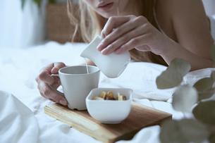 爽やかな朝に寝室のベッドでくつろぐ女性の写真素材 [FYI04675268]