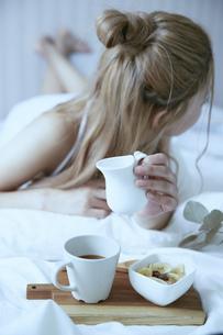 爽やかな朝に寝室のベッドでくつろぐ女性の写真素材 [FYI04675277]