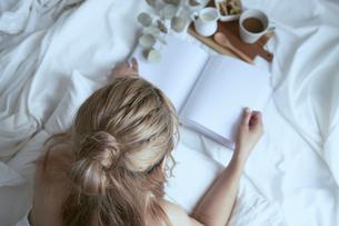 爽やかな朝に寝室のベッドでくつろぐ女性の写真素材 [FYI04675279]