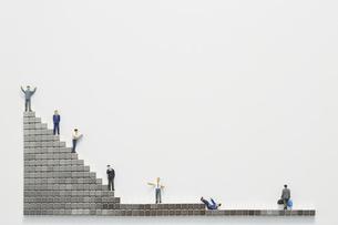 ビジネスマンのミニチュアと階段状に置かれたマグネットブロックの写真素材 [FYI04676144]