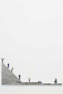 ビジネスマンのミニチュアと階段状に置かれたマグネットブロックの写真素材 [FYI04676145]