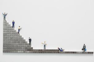 ビジネスマンのミニチュアと階段状に置かれたマグネットブロックの写真素材 [FYI04676146]