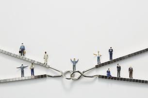 ビジネスマンのミニチュアと知恵の輪とマグネットブロックの写真素材 [FYI04676154]
