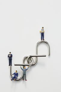 ビジネスマンのミニチュアと知恵の輪の写真素材 [FYI04676155]