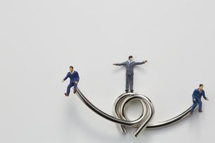 ビジネスマンのミニチュアと知恵の輪の写真素材 [FYI04676156]