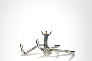 ビジネスマンのミニチュアと知恵の輪の写真素材 [FYI04676158]
