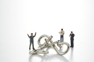ビジネスマンのミニチュアと知恵の輪の写真素材 [FYI04676159]