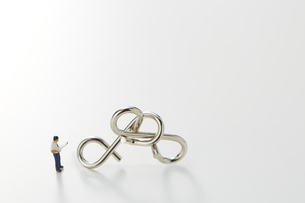 ビジネスマンのミニチュアと知恵の輪の写真素材 [FYI04676160]