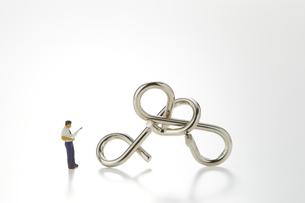 ビジネスマンのミニチュアと知恵の輪の写真素材 [FYI04676162]