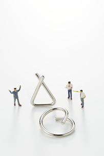 ビジネスマンのミニチュアと知恵の輪の写真素材 [FYI04676163]