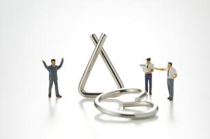 ビジネスマンのミニチュアと知恵の輪の写真素材 [FYI04676164]