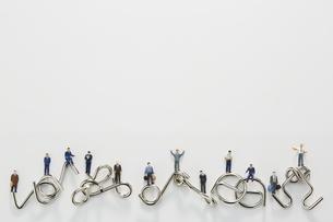 ビジネスマンのミニチュアと知恵の輪の写真素材 [FYI04676166]
