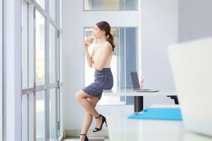 オフィスでコーヒーを飲む美人ビジネスウーマンの写真素材 [FYI04676168]