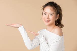 おすすめのジェスチャーをする若い女性モデルの写真素材 [FYI04676169]