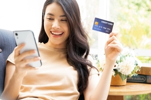 クレジットカードでオンラインショッピングを楽しむ若い女性の写真素材 [FYI04676170]