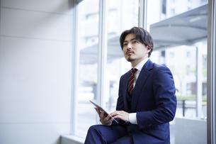 座ってタブレットを操作するスーツ姿の男性の写真素材 [FYI04676216]