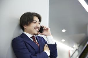 壁にもたれながら電話をするスーツ姿の笑顔の男性の写真素材 [FYI04676218]