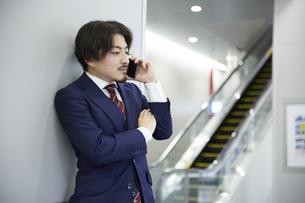 壁にもたれながら電話をするスーツ姿の男性の写真素材 [FYI04676219]